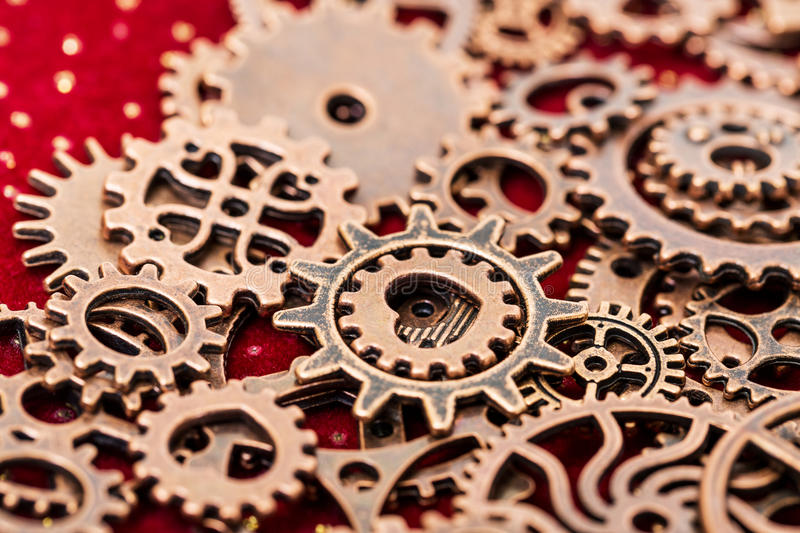 Vintage Mechanical Cogwheel Gears Wheels. Close up on red background stock photos