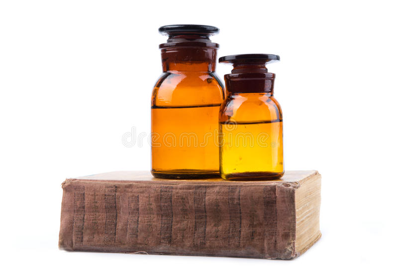 Vintage medicine pharmacy bottles with book. On white background stock image