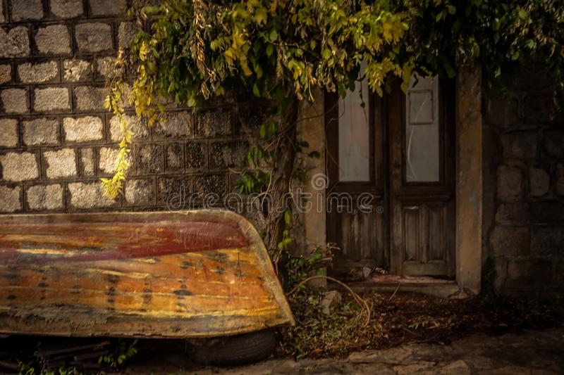 Vintage medieval building exterior on backyard with overturned old vintage sail boat in overcast day during raining autumn season stock images