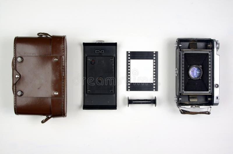 Vintage Medium Format Film Camera Components Organized on a White Background. Vintage rangefinder folding film camera components arranged on a white background stock images