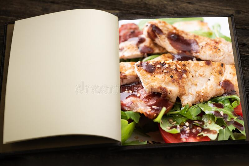 A vintage menu book and image as insert. A chicken salad with rucola bacon and tomato stock image