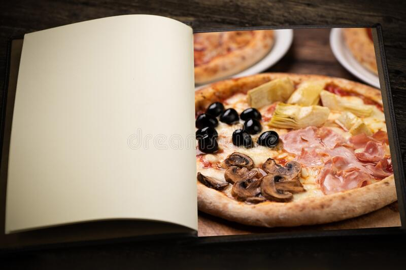 A vintage menu book and image as insert. izza four seasons on a light wooden background stock images