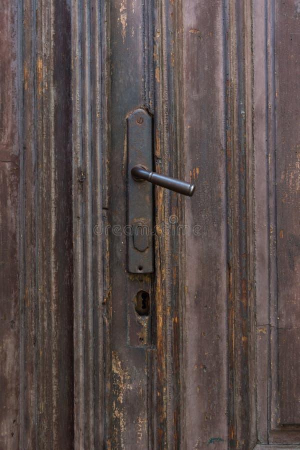 Vintage metal black and rusty door handle. Old wooden brown doors stock photos