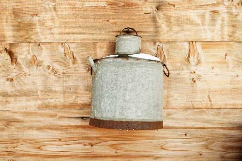 Vintage metal bucket hanging on wooden wall stock image