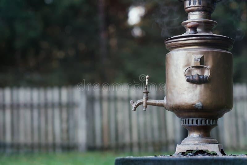 Vintage metal copper tea samovar on nature background. stock photography