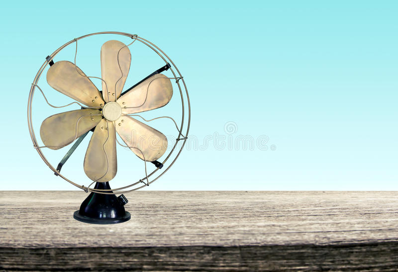 Vintage metal fan on wooden table stock images
