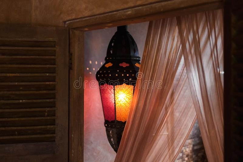 Vintage metal lamp inside room with warm light. Moroccan style royalty free stock photo