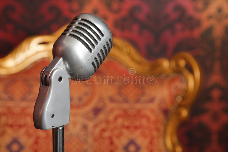 Vintage metal microphone against wallpaper royalty free stock image