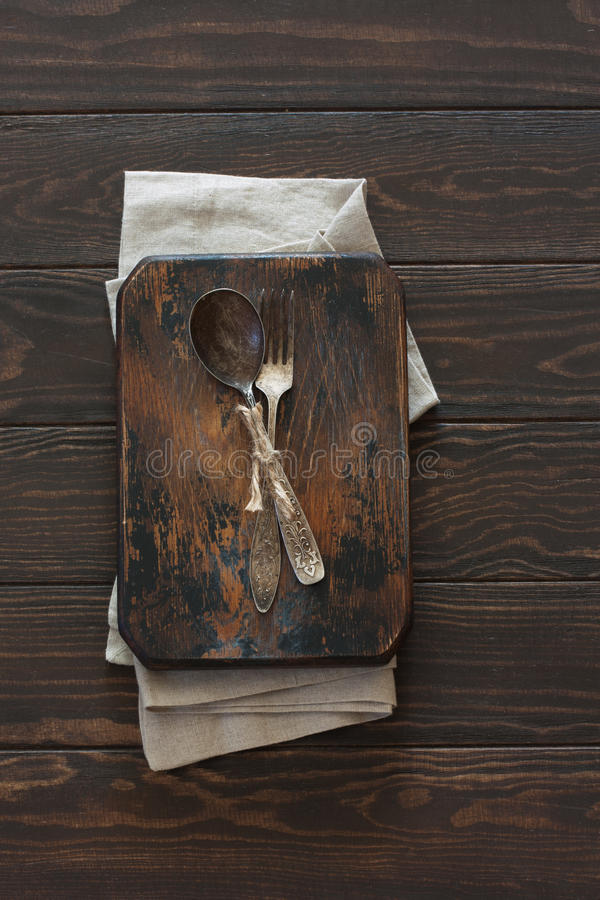 Vintage metal spoon and fork on a wood dark background stock photos