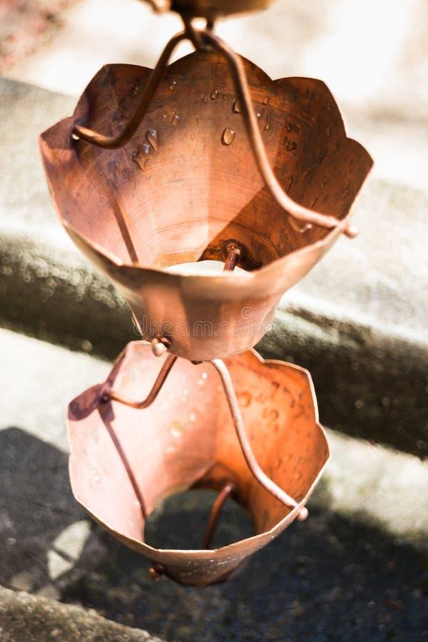 Vintage metallic bells used for rain waters way-out in zen garden. Stock photo stock image