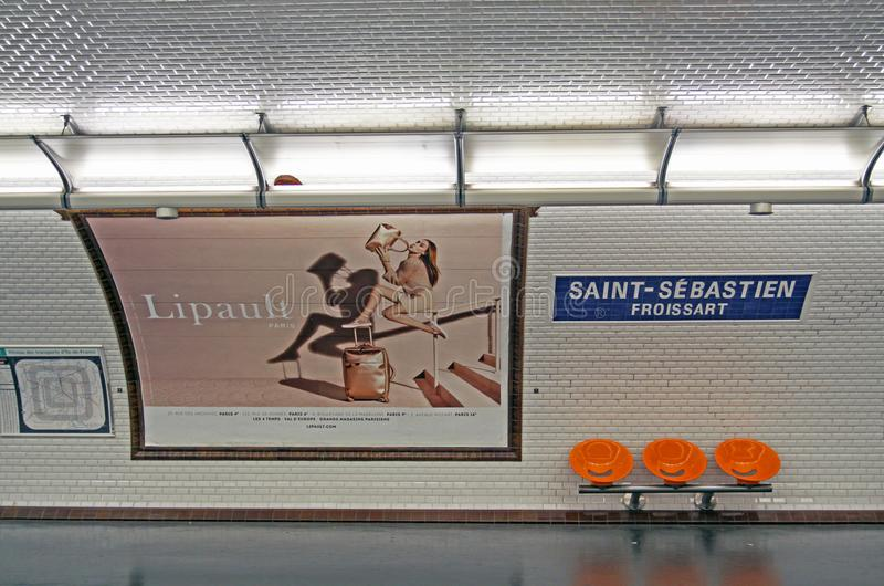 Vintage metro station in Paris. PARIS , FRANCE - JULY 23 ,2017: Paris metro station saint - sebastien with orange benches and old white tiles on the wall stock photo