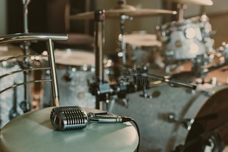 vintage microphone lying on chair in front of stock images