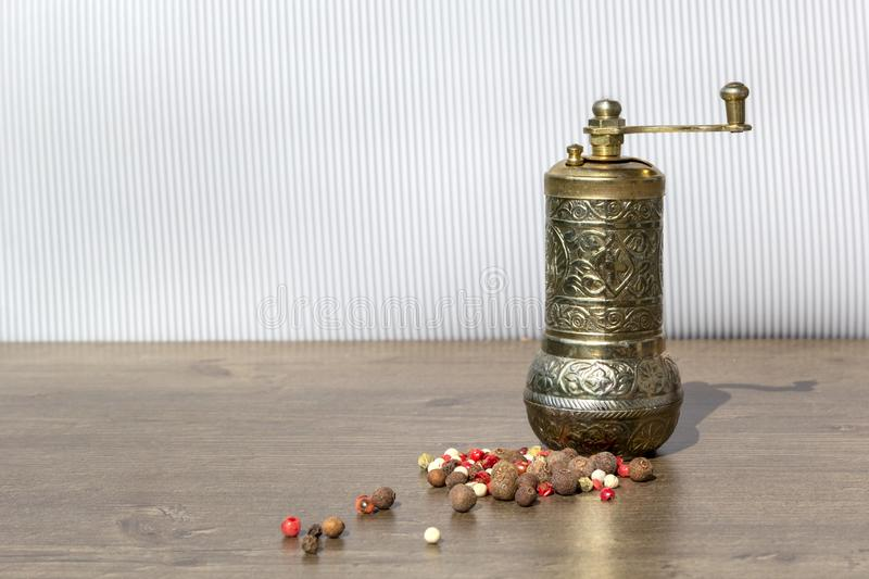 Vintage mill for pepper with black peppercorns and allspice on wooden table. Kitchen appliances for grinding spices and salt royalty free stock photo