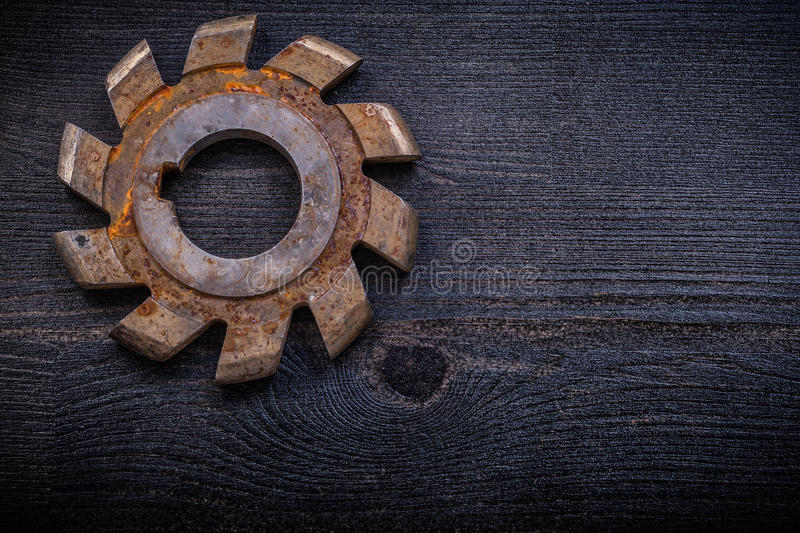 Vintage milling cutter with cogs on wood board. Construction concept stock images