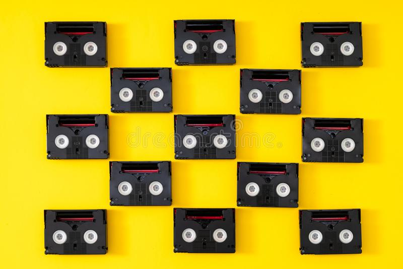 Vintage mini DV cassette tapes used for filming back in a day. Pattern made of plastic video tapes on yellow background royalty free stock images