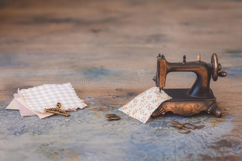 Vintage mini sewing machine with scissors, buttons and fabric on rustic background stock photos