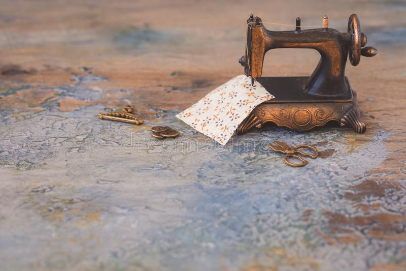 Vintage mini sewing machine with scissors, buttons and fabric on rustic background royalty free stock image