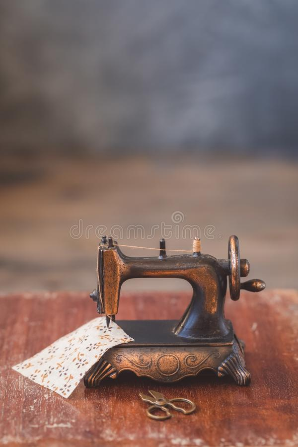 Vintage mini sewing machine with scissors, buttons and fabric on rustic background stock photo