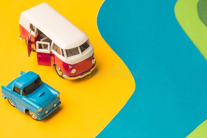 Vintage miniature car and bus in trendy color, travel concept. The toys - vintage miniature car and bus on trendy colored paper. The pop art and creativity stock photography