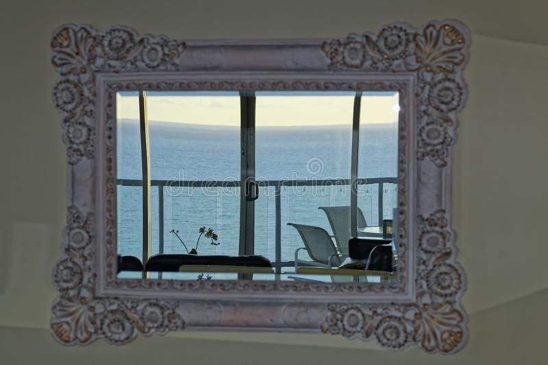 Retro mirror in living room with view to ocean from top floor apartment stock photo