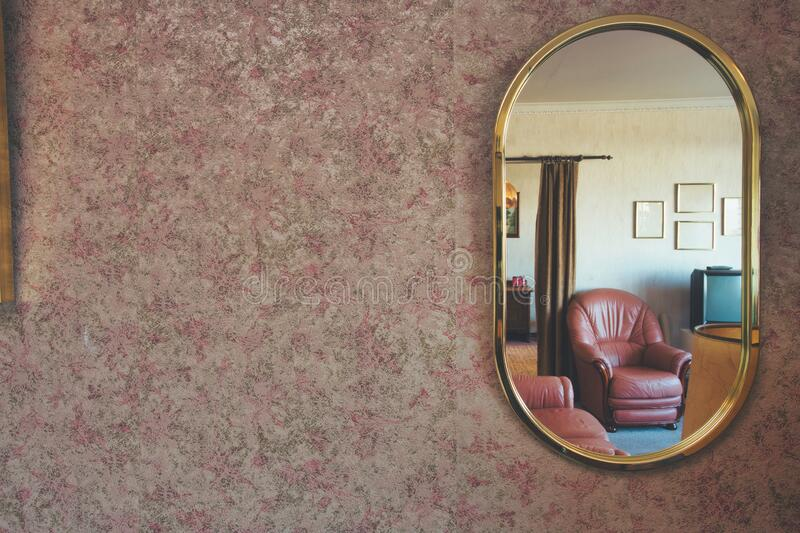 Vintage mirror with patterned wallpaper and a antique livingroom visible in the mirror space for text. Colorful royalty free stock images
