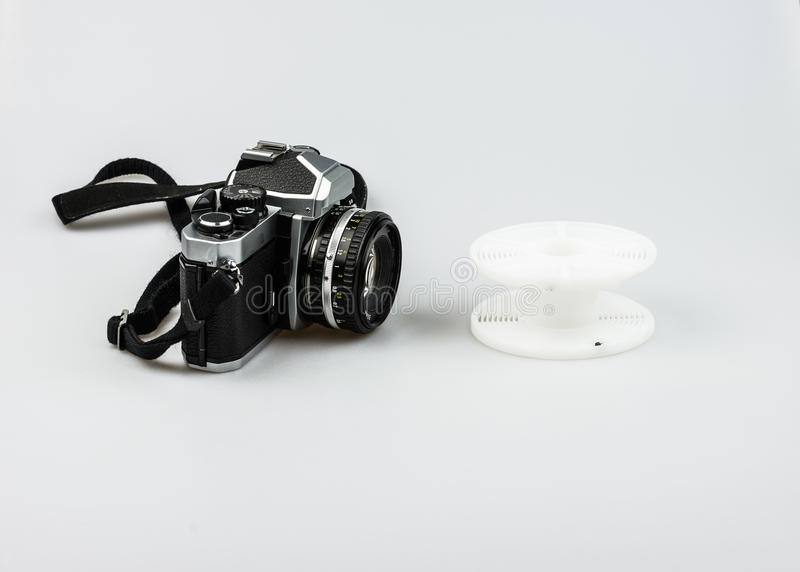 Vintage 35mm analog camera and developing spiral. On a white background royalty free stock images