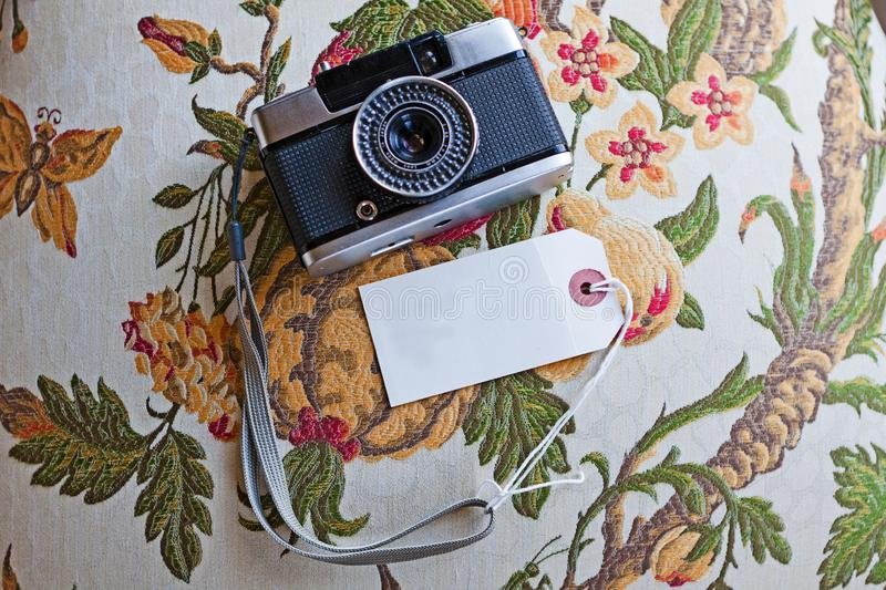 Vintage 35mm antique camera on a floral design table. With a blank name tag stock photos