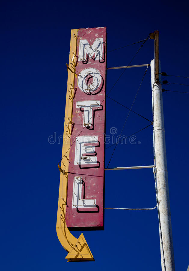 Vintage Motel Sign. A vintage motel sign with an arrow in frount of blue sku stock images
