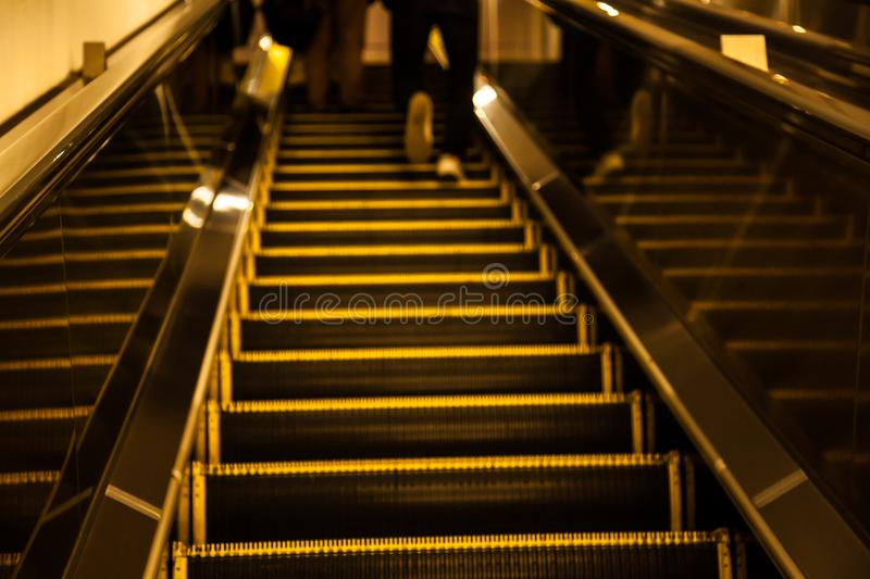 Vintage Motion Blurred man hurry walking up escalator during the rush hours in metropolitan subway shopping mall urban area stock image
