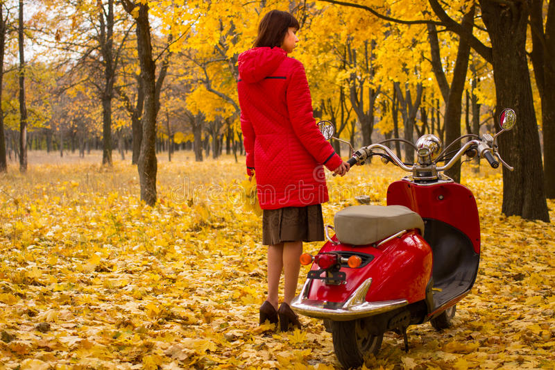 Vintage motorcycle in the autumn forest. A girl with a red retro bike in the beautiful autumn forest royalty free stock image