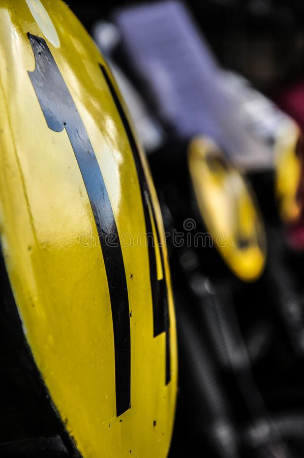 Vintage motorcycle numbers on classic motorbikes at the Goodwood Revival. Dark. Old. Aged. Yellow discs. Retro royalty free stock images