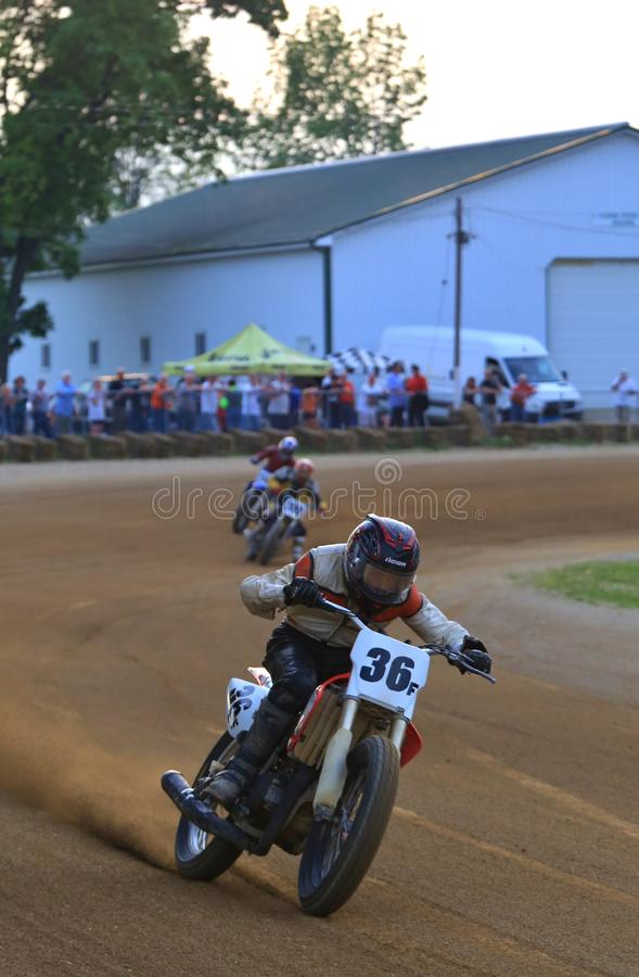 Vintage motorcycle race. Racing motorcycles make the tight turn on the racing track at the vintage motorcycle racing event on the dirt oval flat track speedway royalty free stock photo