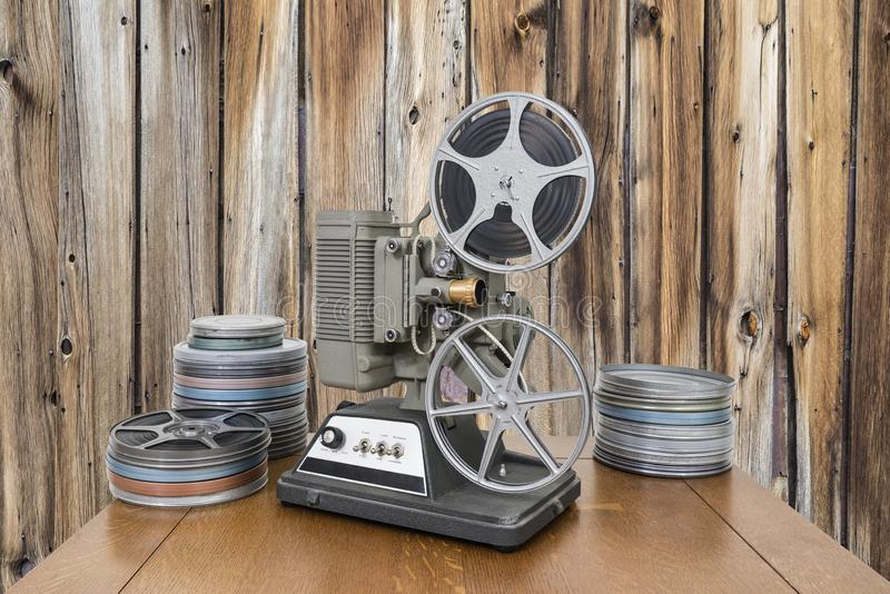 Vintage Movie Projector and Film Cans with Old Wood Wall. Vintage 8mm home movie projector and film cans with old wood wall stock photos