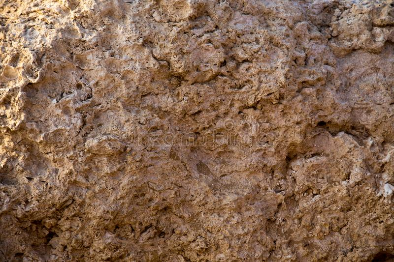 Vintage mud wall in the desert made with beach rocks and coral stones. Texture of stone old wall, old dry coral of brown color. Vintage mud wall in the desert royalty free stock photos