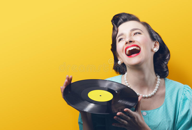 Vintage music. Happy woman with a vinyl record in her hands stock photos
