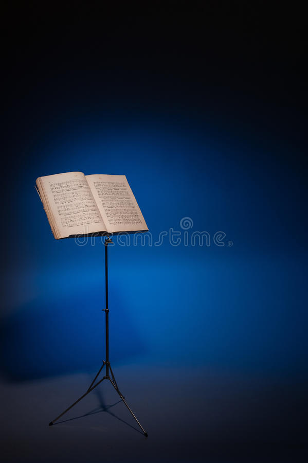 Music stand with vintage piano music. Vintage music on stand on atmospheric blue background
