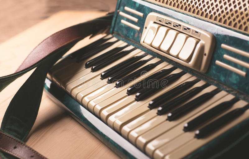 Vintage musical instrument accordion on wooden table royalty free stock photography