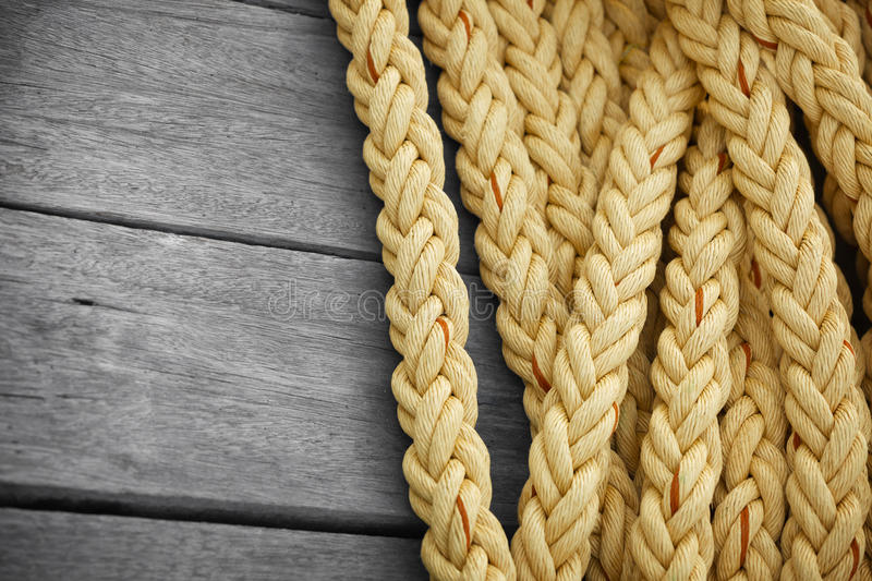 Vintage nautical knots background with copy-space. Big marine sea ropes on wooden desk stock image