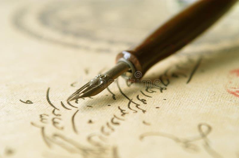 Vintage nib pen. Closeup of an old nib pen with handwrite as background royalty free stock photo
