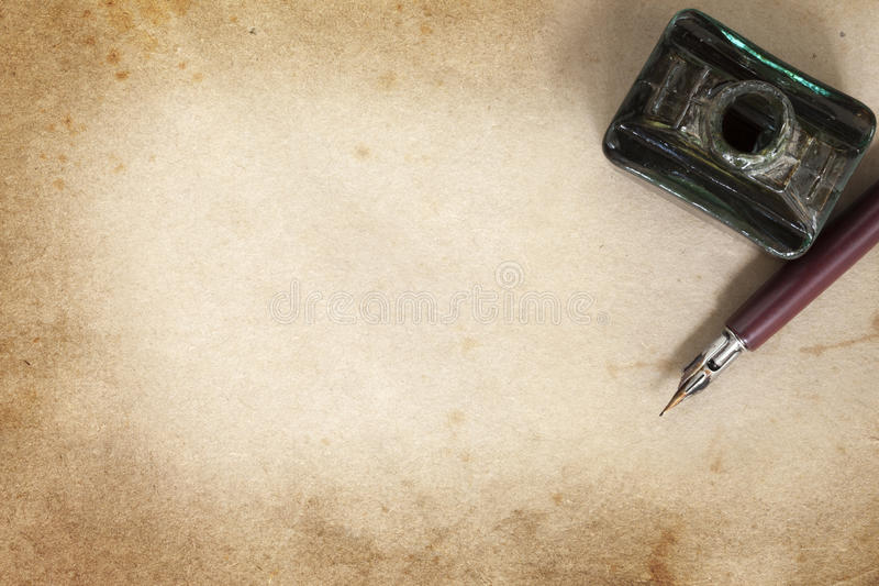 Vintage Nib Pen and Inkwell over Grunge Paper. Vintage nib pen and inwell, over grunge paper royalty free stock photo