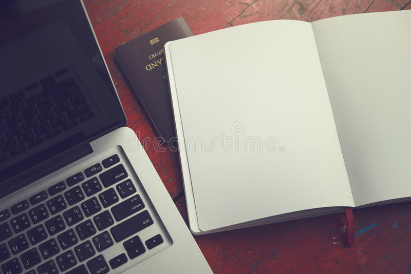 Vintage notebook, passport and computer on red wooden table royalty free stock photography