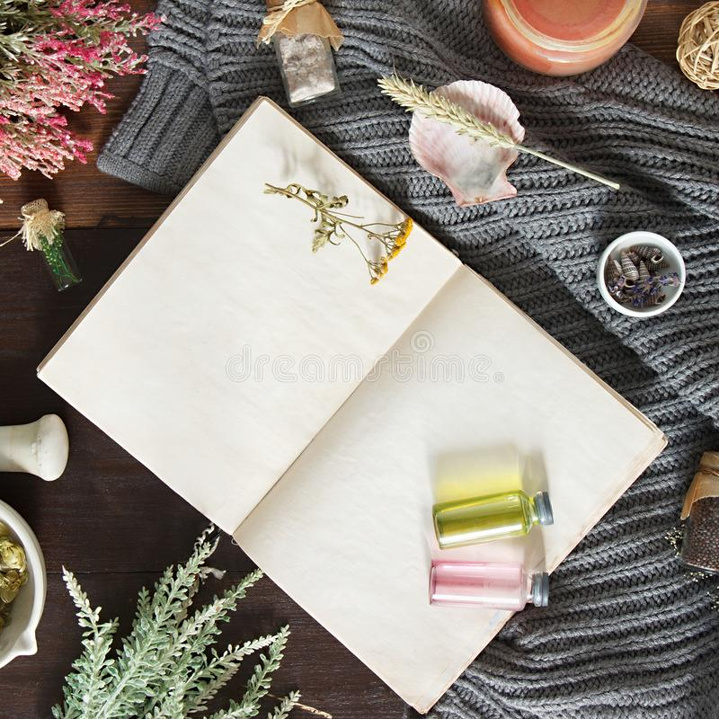 Vintage notebook surrounded by herbs, alchemy appliances, potions and ingredients lies on a dark wooden table. Halloween occultism. Background. Flat lay with royalty free stock photos