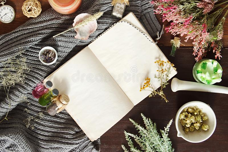 Vintage notebook surrounded by herbs, alchemy appliances, potions and ingredients lies on a dark wooden table. Halloween occultism. Background. Flat lay with royalty free stock image