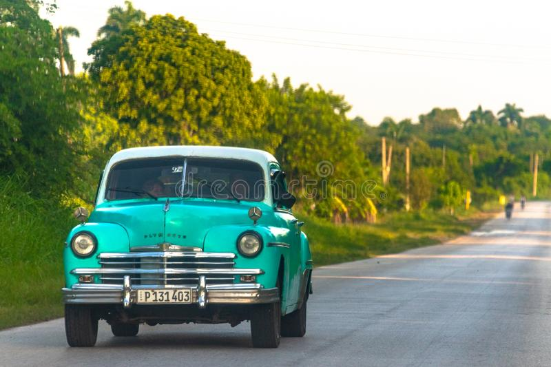 Vintage obsolete car driving in road, Cuba. Vintage old green car driving on a rural Cuban road during the day. Obsolete cars in working conditions have become a royalty free stock photography