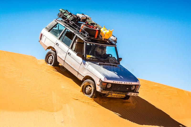 Vintage off road car driving of the sand dune in Merzouga, Erg Chebbi in Morocco royalty free stock photo