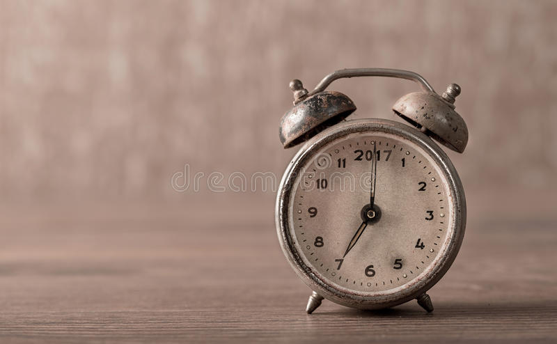 Vintage, old alarm clock on wooden. Background stock photo