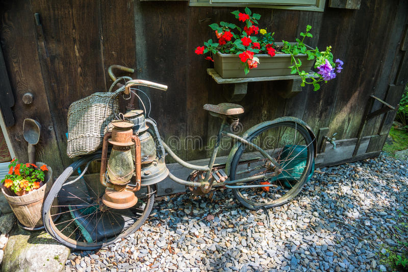 Vintage old bike and lanterns leaning against a house. Vintage old bike with basket and lanterns hanging on handlebars and very flat tires leaning against a wall royalty free stock photo
