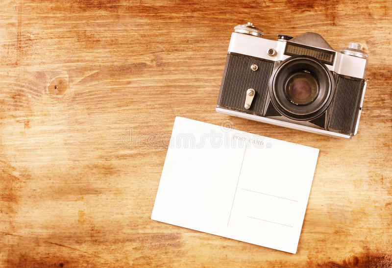 Vintage old camera and postcard. On wooden background. room for text royalty free stock photos