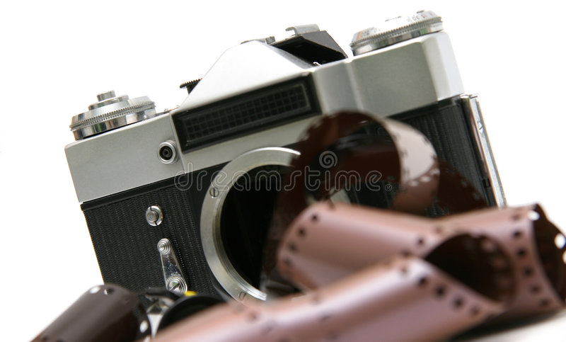 Vintage old film camera with film strip. Professional old film camera, with film strip. Isolated on white background royalty free stock images