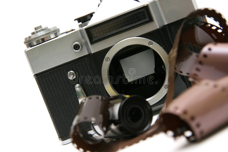 Vintage old film camera with film strip. Professional old film camera, with film strip. Isolated on white background stock images